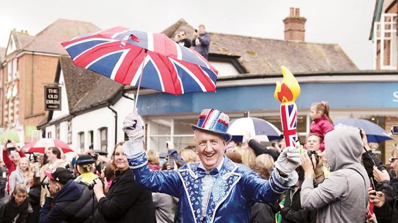 居民盛装迎接火炬  据2012伦敦文化节官网介绍,奥运圣火抵达英国汉普郡的彼得斯菲尔德(Petersfield)时,居民们冲到大街上狂欢庆祝,甚至有人站到屋顶上拍照。图为一位当地居民盛装迎接火炬到来,一手握着充气火炬,一手举着米字旗图案的雨伞,满脸喜悦。   街道彩旗飘飘    奥运期间的伦敦真是欢乐多,这一点当你走在市中心时,尤感明显。(看到图中远处的五星红旗了么?)   在今年五六月间庆祝现任女王钻禧之庆时,伦敦著名的购物街摄政街(Regent Street)、牛津街(Oxford Road)等从不缺